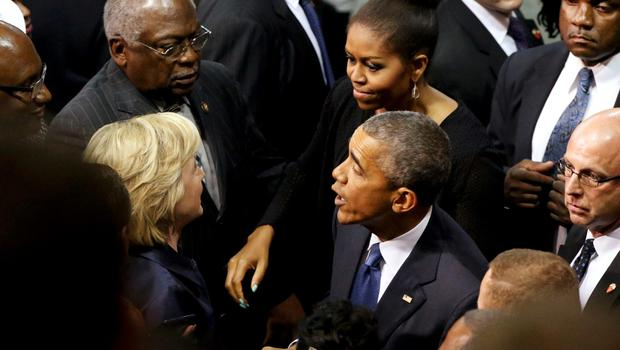 U.S. Democratic presidential candidate Hillary Clinton (L) and U.S. Rep. James Clyburn (top L) talk with first lady Michelle Obama and President Barack Obama after the conclusion of funeral services for Rev. Clementa Pinckney in Charleston, South Carolina June 26, 2015. Pinckney was one of nine victims of a mass shooting at the Emanuel African Methodist Episcopal Church.   REUTERS/Jonathan Ernst