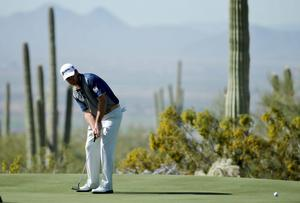 Graeme McDowell watches a putt on the first green during a practice round in Arizona