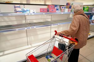 An elderly woman stands before empty shelves of sold out toilet paper and paper towels at a drug store in Berlin, Germany. Photo: Sean Gallup/Getty Images