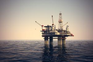 Image of oil platform while cloudless day. Oil platform on sea is offshore structure with facilities to drill wells, extract and process oil and natural gas and temporarily store produced goods until it can be brought to the shore for refining.