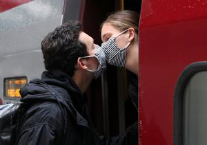 Henri de Chassey wearing a protective face mask, kisses his partner Margaux Rebois, who is returning to Paris after spending 2 months in Brussels, at Midi/Zuid station on the first day of the easing of lockdown measures during the outbreak of the coronavirus disease (COVID-19), in Brussels, Belgium. Photo: REUTERS/Yves Herman