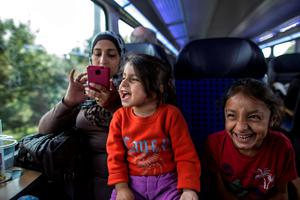 Abeer, 26, a Syrian migrant from Deir al-Zor, uses her mobile phone while her daughters Yasmine, 6 (R), and Hanine, 3, jokes with their father Ihab as they travel from Hamburg to Lubeck, Germany, in this September 18, 2015 file picture.EREUTERS/Zohra Bensemra/Files