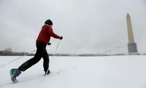 A woman skis along the National Mall towards the Washington Monument in Washington