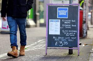 A man walks past an advertising board outside the Simply Crispy sandwich cafe in Belfast, northern Ireland January 12, 2015. REUTERS/Cathal McNaughton