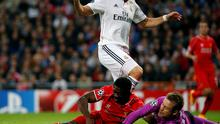 Liverpool's goalkeeper Simon Mignolet and teammate Kolo Toure clash as they stop a ball past  Real Madrid's Karim Benzema