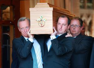 The remains of Liam Healy are carried by Vincent Crowley, former Chief Executive of Independent News and Media, with James Cosgrave and Liam's son Eoin Healy.