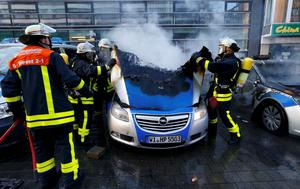 Fireworkers extinguish police vehicles set of fire by anti-capitalist 'Blockupy' protesters near the European Central Bank (ECB) building before the official opening of its new headquarters in Frankfurt