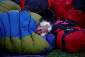 A tourist from the Netherlands waiting for her flight sleeps in a sleeping bag at Tribhuvan International Airport after returning from the Everest Base in Kathmandu, Nepal April 28, 2015. REUTERS/Navesh Chitrakar