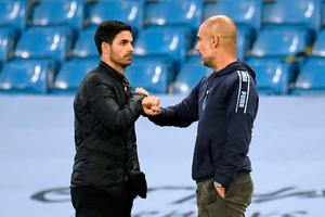 Arsenal manager Mikel Arteta (left) and Manchester City manager Pep Guardiola fist bump after the match. Photo: Peter Powell/PA Wire/NMC Pool