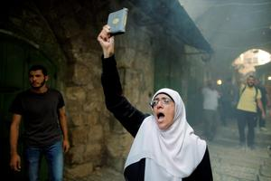A Palestinian woman shouts slogans as she holds a Koran during clashes with Israeli police forces in Jerusalem's Old City  REUTERS/Ammar Awad