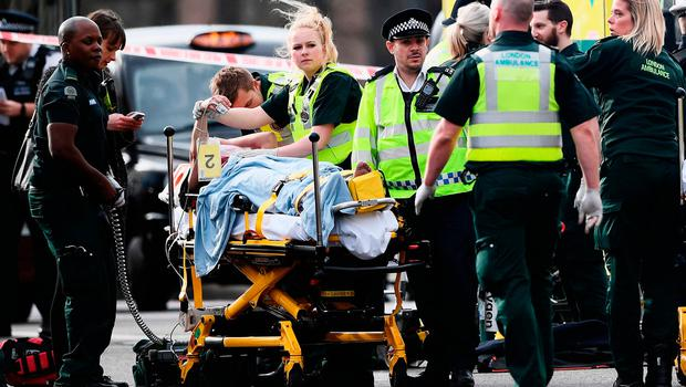 An injured member of the public is treated by emergency services near Westminster Bridge in London after the terror attack. Photo: Carl Court/Getty Images
