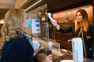 An employee at reception desk protected by plexiglass mesasures the temperature of hotel staff at the lobby of the Athens Palace hotel, on the first day of the opening of hotels in Greece (Photo by Milos Bicanski/Getty Images)