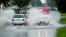 Cars struggling to get through floods on Hyde Road, in Limerick City, yesterday. Photo: Arthur Ellis