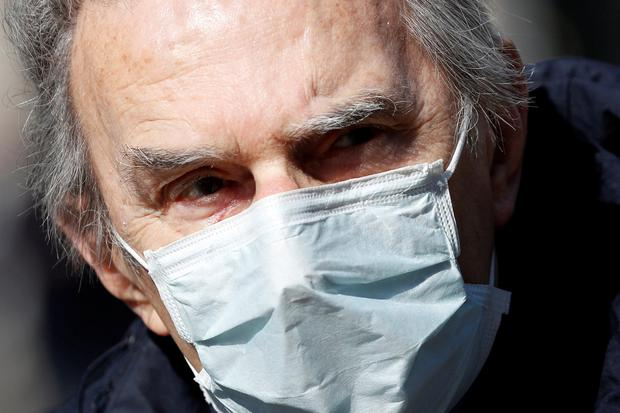 An elderly man wears a protective face mask to prevent contracting the coronavirus in Milan, Italy. Photo: REUTERS/Guglielmo Mangiapane