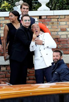 Irish singer Bono, lead vocalist of band U2, jokes with a hotel staff before boarding a taxi boat transporting guests to the venue of a gala dinner ahead of the official wedding ceremony of U.S. actor George Clooney and his fiancee Amal Alamuddin