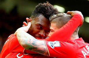 Liverpool's English striker Daniel Sturridge (L) celebrates after scoring his team's third goal during the English Premier League football match between Liverpool and Aston Villa at the Anfield