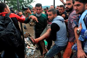 Migrants hold up an injured individual after clashes with Macedonian police near the town of Idomeni on the Greek -Macedonian border on August 21, 2015. Macedonian police have reinforced control at the border with Greece in a bid to stop the influx of migrants, but a few hundred Syrians managed to cross the frontier overnight into August 21. Police prevented reporters to access a no-man's land where on August 20, officers had been in a standoff with about 1,500 migrants and refugees who wanted to cross into Macedonia. AFP PHOTO /SAKIS MITROLIDISSAKIS MITROLIDIS/AFP/Getty Images