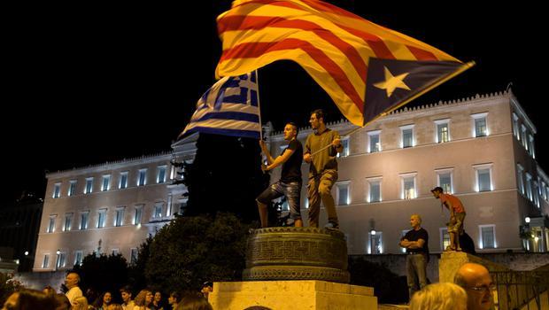 """Protesters wave a """"Estelada"""" (Catalonian separatist flag) (R) and a Greek flag in front of the parliament building during an anti-austerity rally in Athens, Greece, June 29, 2015. Stunned Greeks faced shuttered banks, long supermarkets lines and overwhelming uncertainty on Monday as a breakdown in talks between Athens and its international creditors plunged the country deep into crisis.  REUTERS/Marko Djurica"""