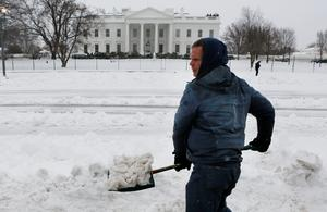 Peace activist Barry Knight clears snow at a peace vigil tent along Pennsylvania Avenue in front of the White House after the region was pounded with snow overnight around Washington