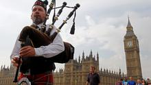 Piper Anton Doherty plays to passers-by in front of the Houses of Parliament on Westminster Bridge in London