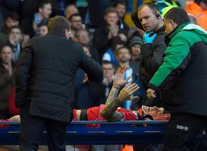 Liverpool's Martin Skrtel (2nd L) talks with manager  Brendan Rodgers as he is carried off the pitch on a stretcher after a challenge with Blackburn's French-born Beninese striker Rudy Gestede.