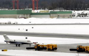 Snow removal equipment (R) is stopped during the clearing of the runways while a small jet readies for take-off at Baltimore Washington International Thurgood Marshall Airport outside Baltimore, Maryland