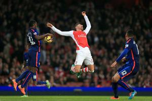 Arsenal's Olivier Giroud (centre) reacts to a challenge from Manchester United's Tyler Blackett (left)