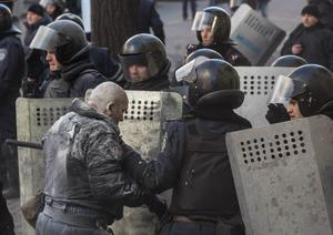 Interior Ministry members help their colleague who was injured during clashes with anti-government protesters in Kiev, February 18, 2014.  REUTERS/Vlad Sodel
