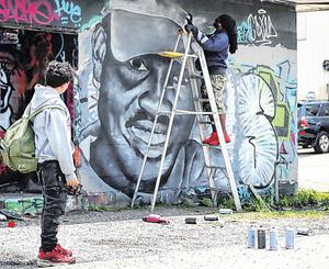 Memorial: A student watches as artist Theo Ponchaveli paints a mural of Ahmaud Arbery in Dallas. Photo: AP