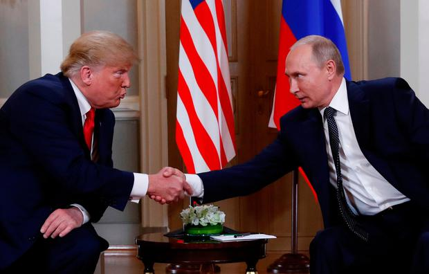 US President Donald Trump and Russia's President Vladimir Putin react as they shake hands during their meeting in Helsinki, Finland July 16, 2018. REUTERS/Kevin Lamarque