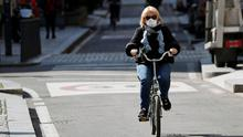 A woman wearing a protective face mask to prevent contracting the coronavirus rides her bicycle in Milan, Italy. Photo: REUTERS/Guglielmo Mangiapane