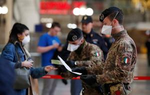 Police officers and soldiers check passengers leaving from Milan main train station, Italy, Monday, March 9, 2020 Areas under lockdown include Milan, Italy's financial hub and the main city in Lombardy, and Venice, the main city in the neighboring Veneto region. (AP Photo/Antonio Calanni)