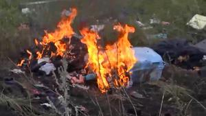 In this image taken from video, Thursday July 17, 2014, showing flames rising from part of the wreckage of a passenger plane carrying 295 people after it was shot down Thursday as it flew over Ukraine, near the village of Hrabove, in eastern Ukraine. AP Photo / Channel 1