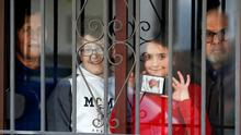A family apart: Cristina Pimentel (8) and brother Daniel (11)show a photo taken by their father of their newborn brother Jesus through a window at their grandparents' house in Ronda, Spain, where they are staying. Photo: REUTERS/Jon Nazca