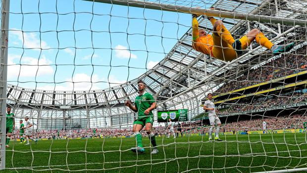 Joe Hart swings from his crossbar after watching a shot go narrowly over