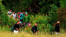 Migrants walk along the border between Austria and Hungary near Heiligenkreuz, about 180 kms (110 miles) south of Vienna, Austria, Saturday, Sept. 19, 2015. Thousands of migrants who had been stuck for days in southeastern Europe started arriving in Austria early Saturday after Hungary escorted them to the border. (AP Photo/Christian Bruna)