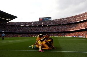 Atletico Madrid's Diego Godin (obscured) is congratulated by teammates after scoring against Barcelona at the Camp Nou