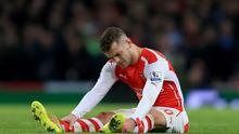 Arsenal's Jack Wilshere sits injured on on the pitch