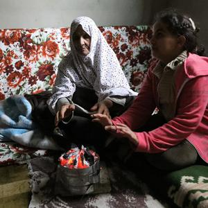 REFUGE: Two women displaced by the fighting in Libya warm their hands at an unfinished apartment in Tripoli, Libya. Photo: Ismail Zitouny/Reuters