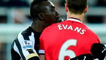 Manchester United player Jonny Evans (r) looks on as Papiss Cisse of Newcastle appears to spit during the Barclays Premier League match between Newcastle United and Manchester United at St James' Park