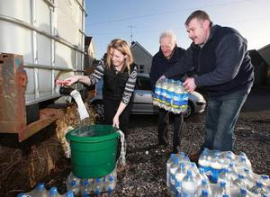Donald Crawford, (right) helps Judity Moutray and Edwin Fletcher to fresh water in Lisbellaw