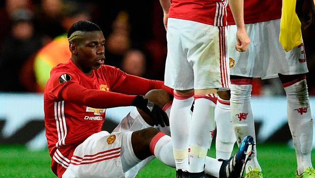 Paul Pogba (L) sits on the pitch injured during the tie at Old Trafford. Photo: AFP/Getty Images