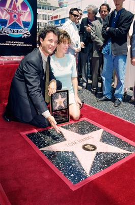 """Actor Tom Hanks shows off his star on the Hollywood Walk of Fame 30 June 1992 during a ceremony honoring movie and television stars. Hanks' current movie, """"A League of Their Own"""" opens tomorrow 01 July. Next to Hanks is his wife, Rita Wilson. AFP PHOTO VINCE BUCCI (Photo credit should read VINCE BUCCI/AFP/Getty Images)"""