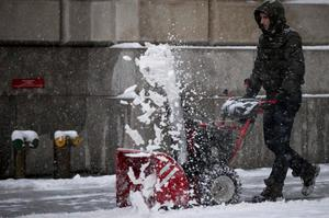 A man clears snow from a sidewalk during the morning commute in New York's financial district near Wall Street