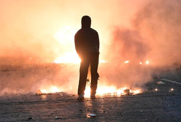 BELFAST, NORTHERN IRELAND - APRIL 07: A person looks on as debris burns during clashes at the Springfield Road/ Lanark Way interface on April 7, 2021 in Belfast, Northern Ireland. (Photo by Charles McQuillan/Getty Images)