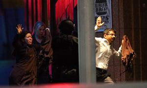 Hostages run towards armed tactical response police for safety right after the police stormed into a cafe under siege at Martin Place in the central business district of Sydney, Australia (AP Photo/Rob Griffith)