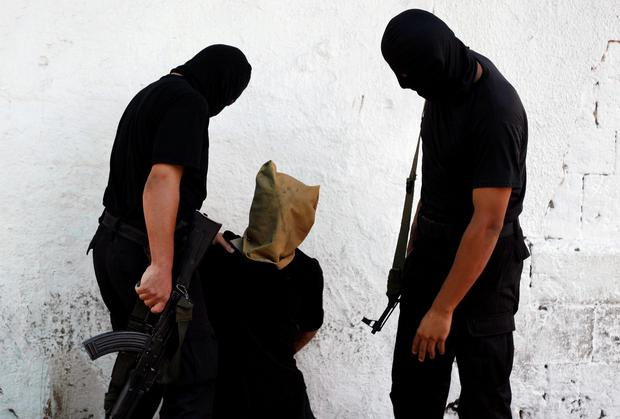 A Hamas militant grabs a Palestinian suspected of collaborating with Israel, before being executed in Gaza City August 22, 2014.