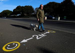 A man walks his dog past a sign encouraging social distancing in Dublin's Phoenix Park. Photo: Brian Lawless/PA Wire