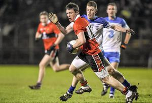 UCC's Shaun Keane keeps possession under pressure from Waterford's Michael Curry