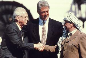 Bill Clinton watches as the Israeli Prime Minister Yitzhak Rabin shakes hands with the Palestinian leader Yasser Arafat in the garden of the White House after the signing of the deal transferring much of the West Bank to Palestinian control